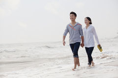 Young couple walking and holding hands by the waters edge on the beach, China stock photography