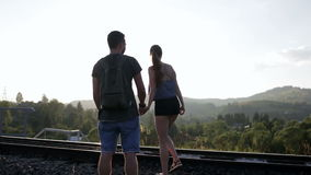 Young couple walking and huging together on old railroad in mountains stock video
