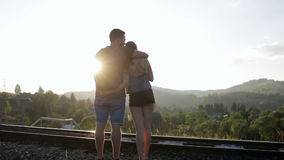 Young couple walking and huging together on old railroad in mountains stock footage