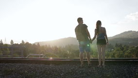 Young couple walking and huging together on old railroad in mountains stock video footage