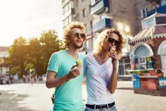 Young couple walking and licking ice cream Royalty Free Stock Photos