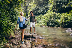 Young couple walking by the mountain stream. With men helping his girlfriend. Couple on hikers in forest by the stream Royalty Free Stock Photos
