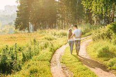 Young couple walking near the forest holding royalty free stock photography