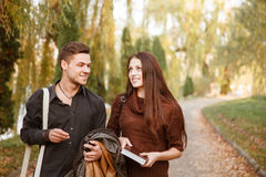 Young couple walking outdoors. Young couple walking in park talking smiling Stock Photo