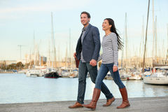 Young couple walking outdoors Port Vell, Barcelona. Young couple walking outdoors in old harbor, Port Vell in Barcelona Catalonia, Spain. Romantic happy women Stock Images