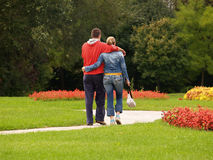 Young Couple Walking In The Park. Young couple walking and hugging each other in the park Stock Image