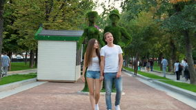 Young couple walking in the park. In the summer sunny day stock footage