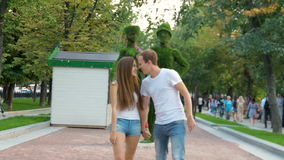Young couple walking in the park. In the summer sunny day. slow motion stock video footage