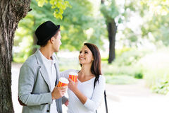 Young couple walking in the park together drinking coffee Royalty Free Stock Photography