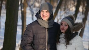 Young couple walking in a park. Winter season. Loving couple walking in winter park and smiling.  stock footage