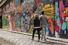 Young couple walking past graffiti wall in Melbourne Stock Images