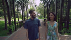 Young couple walking on a path in the park under the arch, chatting and smiling. stock video