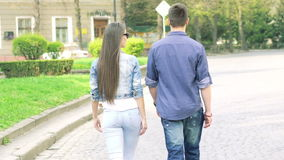 Young couple walking on the pavement. Camera behind them. Slowly stock footage