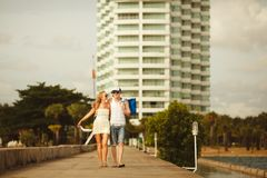 Young couple walking on the pier to the sea. wedding honeymoon places. couples vacation. Young couple walking on the pier to the sea. wedding honeymoon places Stock Photo