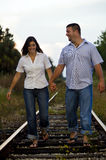 Young couple walking on rail tracks. Couple holding hands walking on railroad tracks though countryside Royalty Free Stock Image