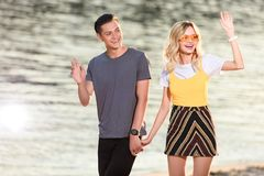 Young couple walking on river beach in evening and waving hands. To someone royalty free illustration