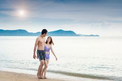 Young couple walking romantic travel honeymoon on beach. In summer holidays Royalty Free Stock Photos