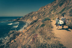 Young couple walking on a rugged trail with their surfboards. In Palos Verdes Estates, California Royalty Free Stock Photo