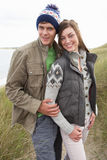 Young Couple Walking Through Sand Dunes. Wearing Warm Clothing Royalty Free Stock Image