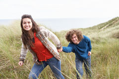 Young Couple Walking Through Sand Dunes. Wearing Warm Clothing Stock Photo