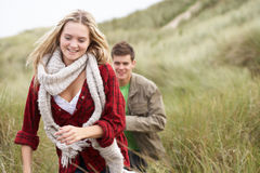 Young Couple Walking Through Sand Dunes. Wearing Warm Clothing Stock Photography
