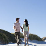 A young couple walking in sand dunes Stock Photo