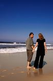 Young couple walking on sandy. Young couple in love walking on sandy beach on a warm winter day stock photos