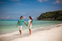 Young couple walking on sandy beach near the sea Royalty Free Stock Photos