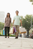 Young couple walking with shopping bags in hands, Beijing, China Royalty Free Stock Images