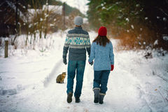 Young couple walking on the snowy road Stock Photo