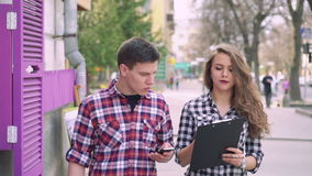 Young couple walking on the street, discussing using phone and notebook. Slowly.  stock video footage