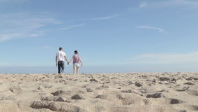 Young couple walking and talking together on the beach stock footage
