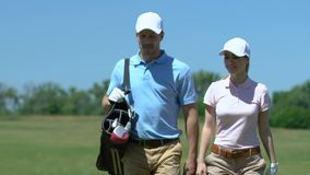 Young couple walking to next hole on golf course, man carrying golf bag, hobby. Stock footage stock video