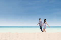 Young couple walking together on the beach Stock Images