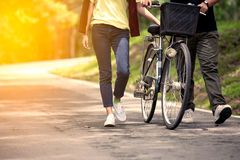 Young couple walking together with bicycle in the garden royalty free stock photo