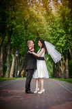 Young couple walking together hand by hand  in summer park Royalty Free Stock Photography