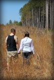 Young couple walking together in meadow Royalty Free Stock Photos