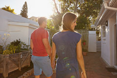 Young couple walking towards their house. Rear view of young couple walking towards their house. Couple in backyard taking walk on a bright sunny day royalty free stock photos