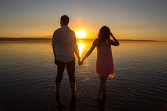 Young couple is walking in the water on summer beach. Sunset over the sea.Two silhouettes against the sun. Just married couple royalty free stock photo
