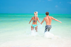 A young couple walking through the waves Royalty Free Stock Image