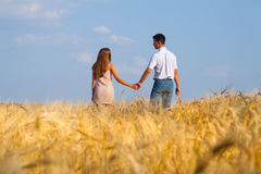 Young couple walking through  wheat field Stock Photo