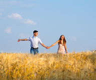 Young couple walking through  wheat field Royalty Free Stock Photos