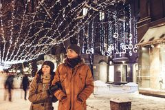 Young couple walking in winter city center under holiday illumination. At night Stock Photos