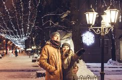 Young couple walking in winter city center under holiday illumination. At night Stock Photography