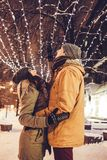 Young couple walking in winter city center under holiday illumination. At night Royalty Free Stock Image
