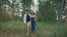 Young couple walking in the woods or the park, not far from his home. A man and a woman love each other, they are happy in the summer evening together stock footage