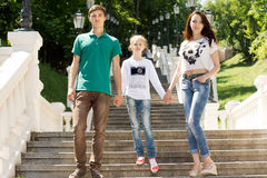 Young couple walking with a young girl Stock Photos