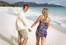 A young couple walks on the beach holding hands Stock Image