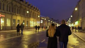 Young couple walks on the night urban illuminated street. The people have a good time together in the evening. Prores codec stock video footage