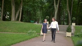 A young couple walks in the park. A young couple of lovers walk along the path in the park. They are holding hands, laughing look at each other. Happy life stock video
